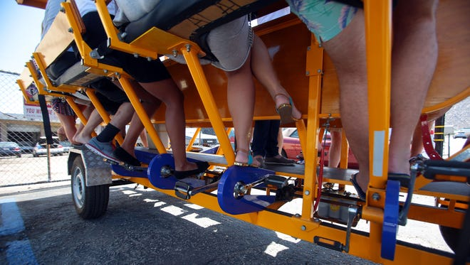 Tourists prepare to tour Palm Springs on Social Cycle's human pedal powered vehicle on Wednesday.