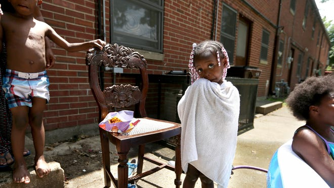 Kay Kirkendall, 2, dries off after playing in a pool with her siblings and friends at Peter G. Noll Apartments in Newport. Kay's mother Kim Kirkendall said she is looking forward to moving because there isn't enough space for her five children to play. The public housing development will be torn down when the Ky. 9 extension is built. This will have a major impact on the west side neighborhood. The housing complex houses 171 families. The relocation will begin sometime this year.