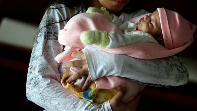 A 13-year-old girl holds her one-month-old baby at a shelter for troubled children in Ciudad del Este, Paraguay, on May 14, 2015. The girl said she was raped by her stepfather from the time she was 10 and became pregnant when she was 12. Another pregnant girl, 11, gave birth on Aug. 13, 2015. The girl was allegedly raped and impregnated by her stepfather when she was 10.
