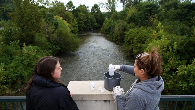 Alyssa Mayer and Barbara McGraw collect water from Mill Creek in Evendale after entering information about creek and weather conditions into the Liquid app.