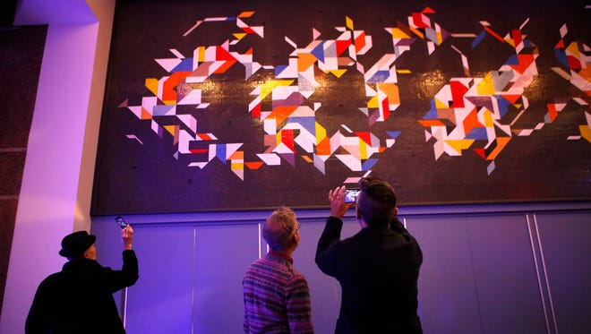 """People photograph Charley Harper's restored mural, """"Space Walk,""""  at The Duke Energy Convention Center Tuesday, November 10, 2015. The abstract constellation was created with  30,000 tiles."""