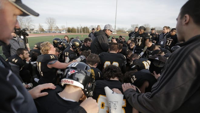 UW-Oshkosh head coach Pat Cerroni, center, talks to his players after the Titans lost to UW-Whitewater in the NCAA Division III national quarterfinal at J.J. Keller Field at Titan Stadium on Saturday, Dec. 5.