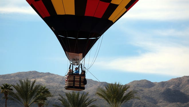 A hot air balloon takes passengers up during the second Cathedral City Hot Air  Balloon Festival on Saturday, February 13, 2016 in front of the Cathedral City Civic Center. 20 balloons are scheduled to lift off and light up the night sky with their burners from 5:00 p.m. to 6:30 p.m.