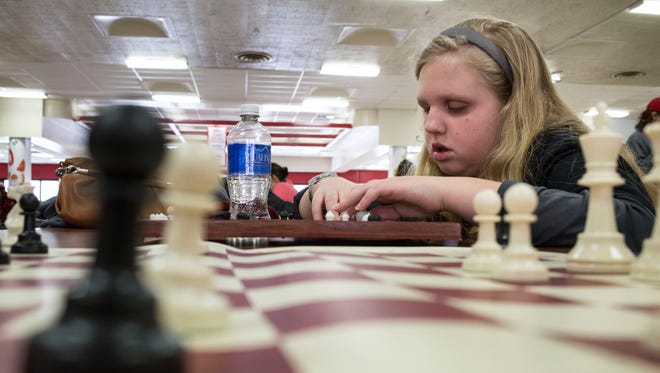 Avery Shutt, 9, uses a braille chess board during the Phil Willard Chess Tournament Saturday, March 5, 2016, at Port Huron High School.