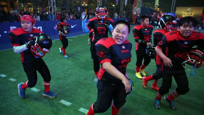 Chinese youths celebrate after winning a game at a National Football League publicity event in Beijing on Oct. 23, 2015.