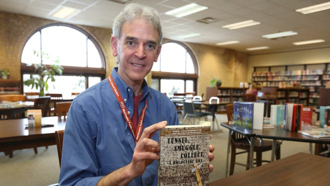 """Milwaukee-based book author and writer Jeffrey Gingold, 56, poses with his latest book, """"Tunnel, Smuggle, Collect: A Holocaust Boy,"""" at Washington Junior High School's library on Wednesday, April 6. The book tells the story of how Gingold's father and grandparents survived the Holocaust in the Warsaw Ghetto in Poland."""