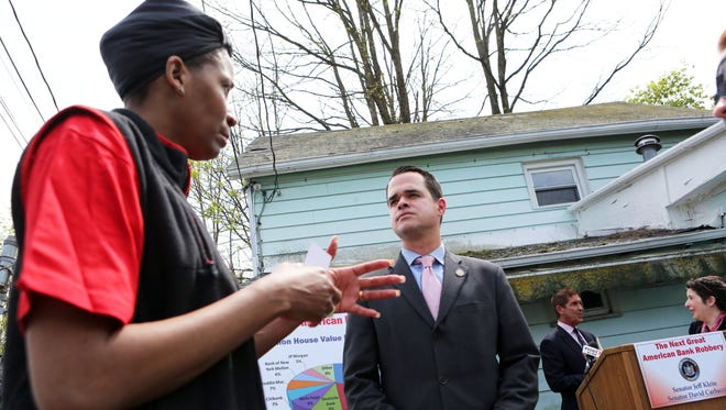 Cassandra Edwards, Executive Director of Advocating for Change, speaks with Senator David Carlucci as Senator Jeff Klein speaks with Stephanie Rojas, Housing Director of the Rockland Housing Action Coalition, after a press conference in front of a zombie property in Spring Valley, May 11, 2016. The senators called for new legislation to monitor bank-owned homes and zombie properties.