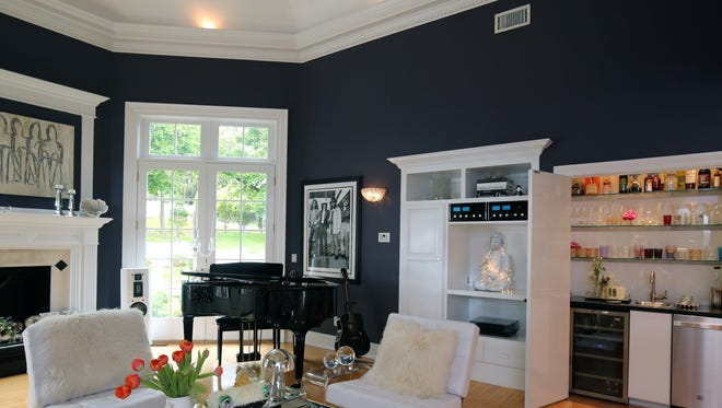The living room of this Upper Nyack home has crown molding, which contrasts with the strong color of the walls.
