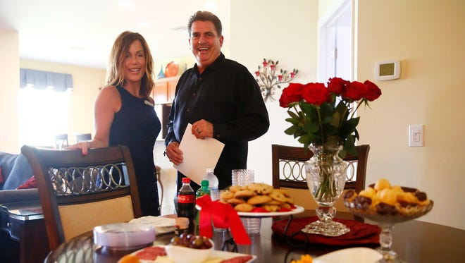 """Tammy Garro, left, and D. Michael Burke, both realtors of Keller Williams Realty, are shown in portrait among their spread of food for potential home buyers Wednesday, May 18, 2016 at an open house at Village Walk of Bonita Springs community of Bonita Springs, Fla. While statistically, the internet lures in home buyers, open houses can draw crowds who want a more traditional approach. In response to the recent housing slowdown, and heading into the off-season some agents are coming up with creative ways to attract buyers, from """"family fun days,"""" to attract buyers when kids are off from school, to television shows to collaborative marketing between agencies. (Corey Perrine/Staff)"""