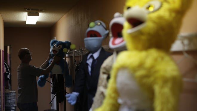 """Richard Lawrence, set builder and puppeteer, straightens puppets before practice for """"Avenue Q,"""" a Fondren Theatre Workshop production at Actor's Playhouse in Pearl."""