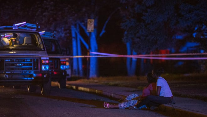 Two women hold one another in the 4400 block of Ralston Avenue Wednesday night where three people were found shot, one fatally, inside a car.