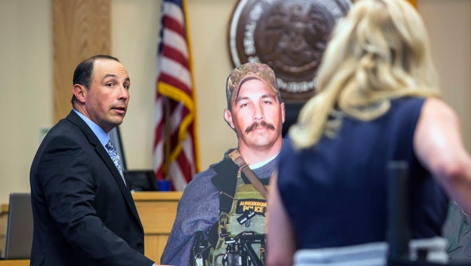 Former Albuquerque police Detective Keith Sandy, stands next to a life-size cut out of himself while assisting the prosecution in demonstrating the distance he maintained during the time of the shooting, Wednesday, Oct. 5, 2016 in Albuquerque, N.M.. Attorneys in the jury trial of two former police officers charged in the killing of a homeless camper have attempted to reconstruct the scene of the standoff that ended with the officers fatally shooting the man in the arms and back.