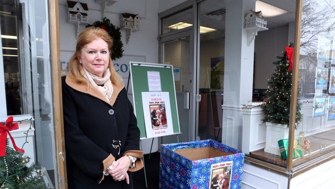 "Marylin Hoffman, sales manager at William Raveis Real Estate in Rye, beside the ""Toys for Tots"" donation box outside the office, Dec. 7, 2016 where about 15 toys were stolen from the box the day before."