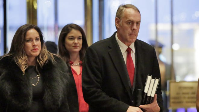 Rep. Ryan Zinke, right, R-Mont., arrives in Trump Tower in New York on Monday.