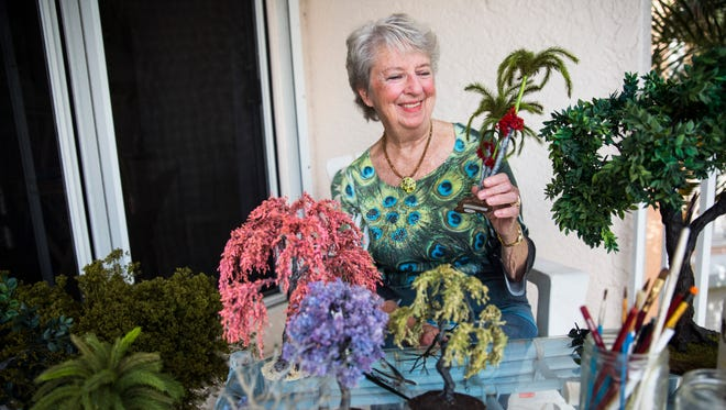 Marilyn Heath Laufer displays a handmade miniature palm tree at her home in Naples, Florida on Thursday, Dec. 15, 2016. Laufer spends hours crafting realistic-looking miniature trees out of her home, and sells them online for around $100 apiece.