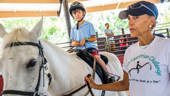 Nicholas Cosentino, 7, of Naples, takes a riding lesson at the Naples Therapeutic Riding Center on Thursday, March 30, 2017. The center just completed a $4 million campus expansion project.