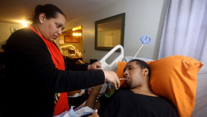 Muriel Daniel holds a glass as her son Jyrel, 22, drinks from a straw in their New Rochelle home May 9, 2017. Jyrel was midway through a five year MBA program at Johnson and Wales University in Rhode Island when he was severely injured in a car accident while home for his brother's high school graduation in June of 2016. Muriel Daniel feels the city of New Rochelle bears some responsibility for the crash, in which a car traveling at a high rate of speed on Lincoln Ave struck the car Jyrel was a riding in.