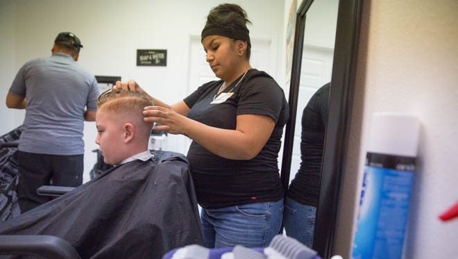 Elijah Werth, 9 gets his hair styled after a haircut by Genesis Vargas, Thursday Aug. 10, 2017 at Glitz School of Cosmetology, The school was giving free haircuts to kids before school starts.