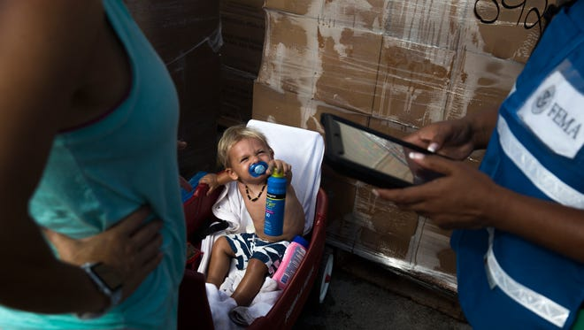 Liza Wells registers with the Federal Emergency Management Agency as her son, Zander, tries to hand her sunscreen, Friday,  in Everglades City, Fla.