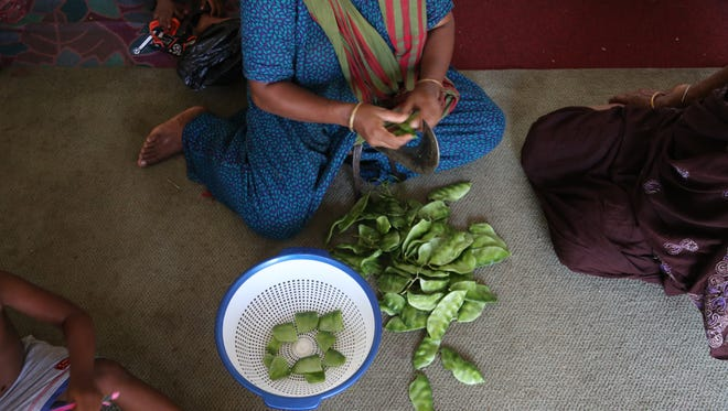 Bandhu Gardens co-founder Minara Begum cuts broad beans on a boti, a large Bengali knife, on the floor of her home in Detroit's Banglatown neighborhood.