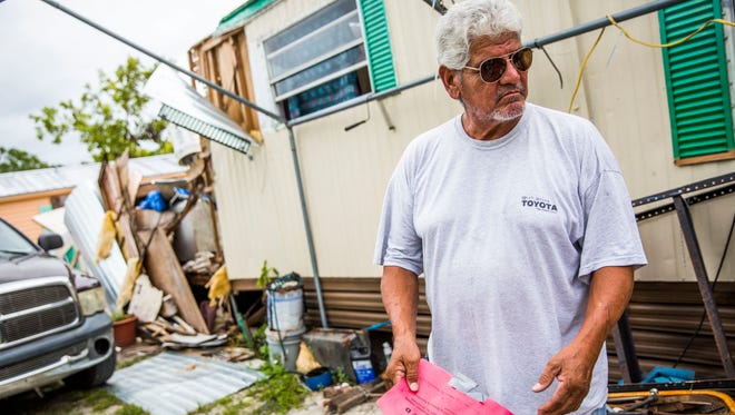 Santiago Rosalez stands outside his severely damaged Immokalee trailer Thursday, Oct. 12, 2017. Rosalez has been sleeping in his truck outside his trailer, and the only thing he has heard from FEMA is instructions on how to apply for a loan, which he says he cannot afford.