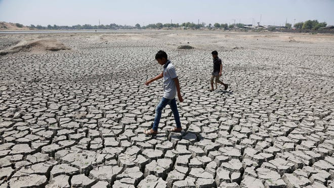 Indian boys on their way to play cricket walk through a dried patch of Chandola Lake in Ahmadabad, on May 14, 2016.
