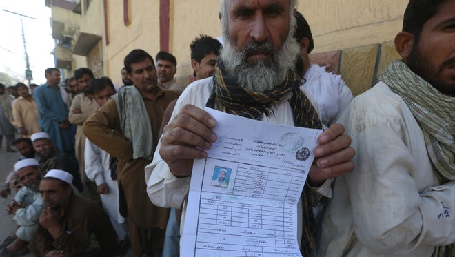 An Afghan refugee who fled his country due to war and famine shows his registration in Peshawar, Pakistan, on Oct. 25.