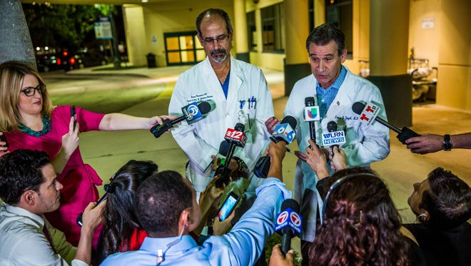 Dr. Louis Yogel, chief of staff, right, addresses the media during a press briefing outside of Broward Health Medical Center. Dr.Benny Menendez, chief of emergency medicine, left, listens.