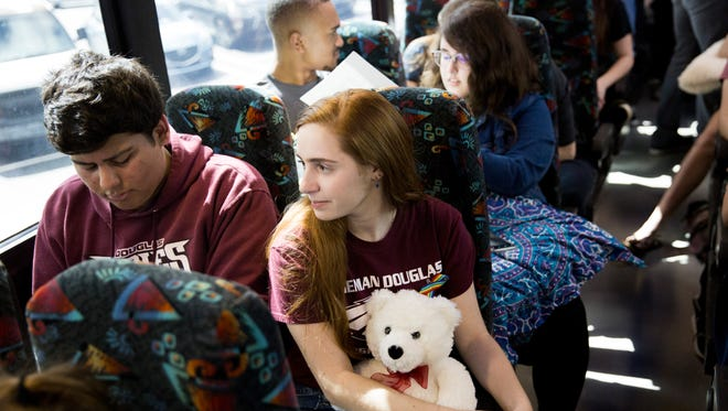 Senior Isabelle Robinson, 17, and 100-plus students from Marjory Stoneman Douglas High School, board a bus outside a Publix Super Market on Tuesday, Feb. 20, 2018, in Parkland, Fla., to make their way to the state capital in Tallahassee, Fla., to advocate for stricter gun control laws.
