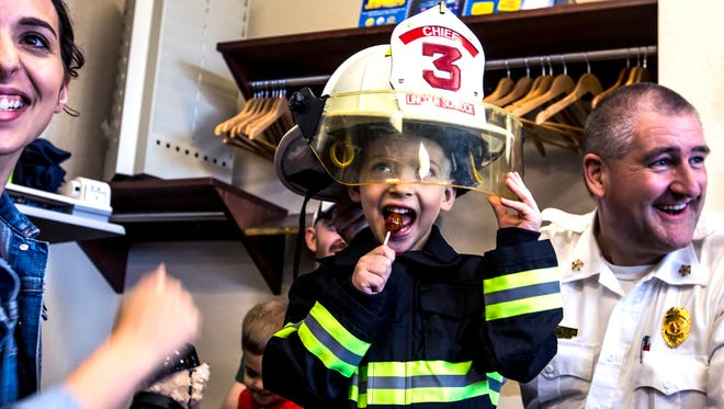 Lincoln Schrock tries on a fire helmet at the Marshfield Fire and Rescue Station in Marshfield, Wis., May 3, 2018.