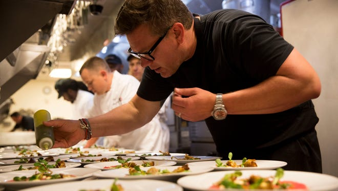 Acclaimed chef Tyler Florence, Food Network host and award-winning winemaker, garnishes an appetizer at Cooper's Hawk Winery & Restaurants during an interactive cooking demonstration, a multicourse dinner with wine pairings and a meet-and-greet on Wednesday, June 20, 2018.