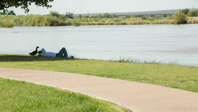 Marcos Castro, rests in the grass along the Rio Grande Trail in La Llorona Park as a duck waddles around him, Friday July 20, 2018. The Rio Grande Trail at La Llorona Park, which with the help of the $35.6 million GO Bond the city wants to finish connecting to the Out Fall Channel Trail, that runs under Main street. Friday July 20, 2018.