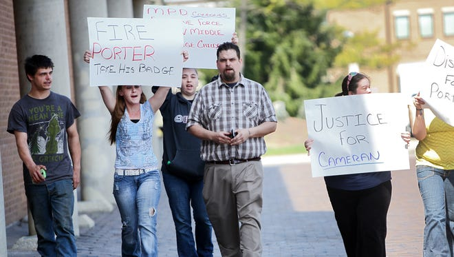 (Center) Clifford Adams, of Middletown, and others, protest outside of the Middletown City Building that houses the Middletown Police Department regarding a Middletown officer that shoved a middle school student to the ground while trying to break up a fist fight at Middletown Middle School on April 13.