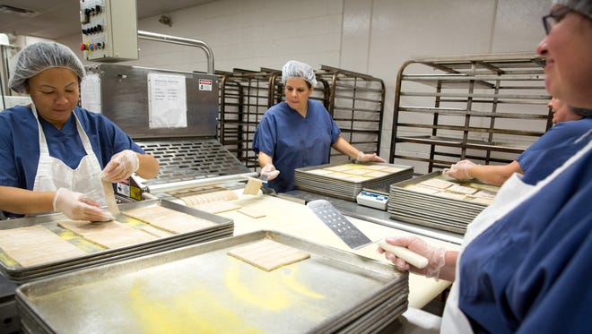 Jessica Vanlo, left, Dana Cran, center, and Sherry Worley, all of Des Moines, place breadsticks onto cookie sheets during Thursday's open house for Des Moines Public Schools' Central Nutrition Center as part of National School Lunch Week.