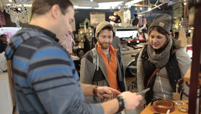 Jesse Stefani of Keego Harbor, owner of Hex Detroit, helps Jordan Ceresnie and Amber Ceresnie of Farmington on Nov. 29 at the Rust Belt Market in Ferndale. Treating customers well is key to keeping them past the holidays.