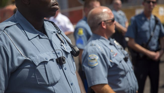 Members of the Ferguson Police department wear body cameras during a rally on August 30 in Ferguson, Missouri.