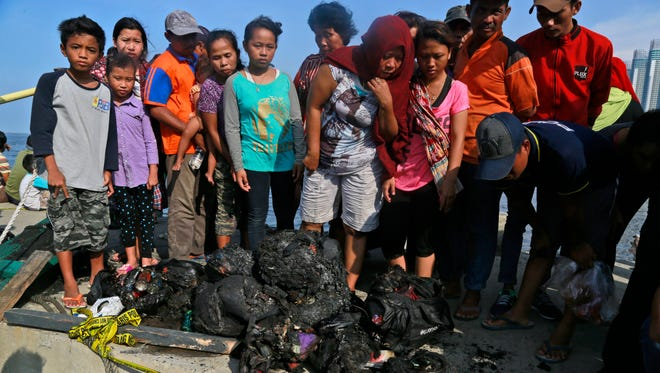 People inspect charred personal belongings of the passengers of a ferry that caught fire off the coast of Jakarta.
