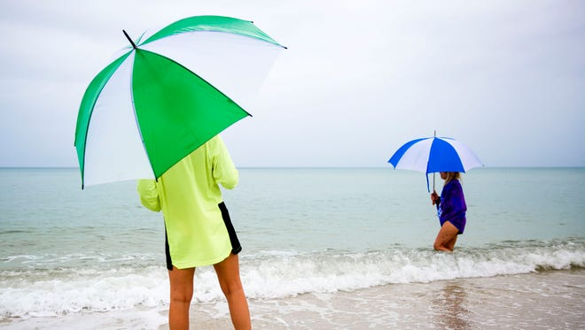 Vacationers wait for the rain to stop on Saturday, May 26, 2018 at Vanderbilt Beach in North Naples. Subtropical Storm Alberto is bringing heavy rain to Collier County through Memorial Day weekend.