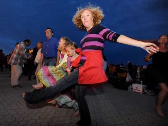 Catherine Wortman dances with her daughters Erin, 9, and Aleena, 8, during Bands on the Beach at the Gulfside Pavilion on Pensacola Beach.