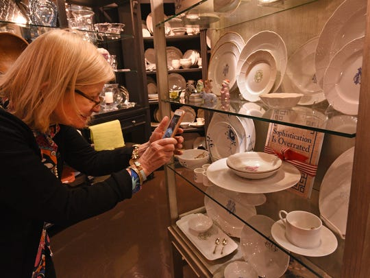 Babs Horner photographs the dishes at Lewis' Gifts.
