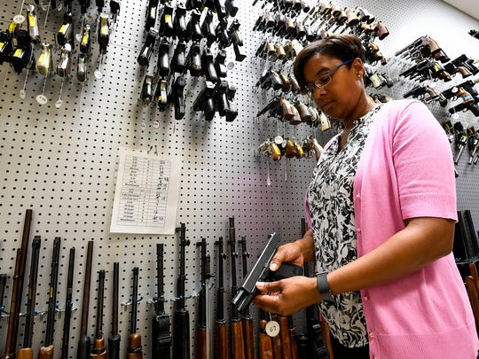Firearms and toolmarks section chief Michelle Cuenco looks through sample guns at the Alabama Department of Forensic Sciences in Montgomery, Ala. on Tuesday May 29, 2018.