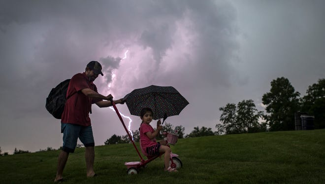 "Ali Alsailawi pushes his daughter Zahraa ""Zuzu"" Alsailawi on a tricycle while lighting goes off in the distance on Wednesday, July 4, 2018, at City Park in Fort Collins, Colo."
