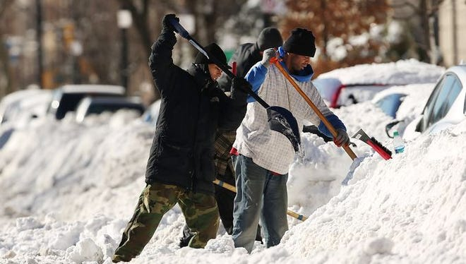 People dig out cars after a blizzard in the Brooklyn borough of New York.