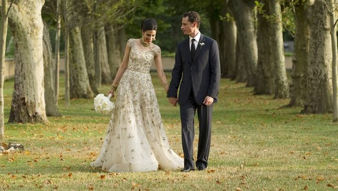 Anthony Weiner walks with his wife, Huma Abedin, during a formal wedding picture shoot in 2012.