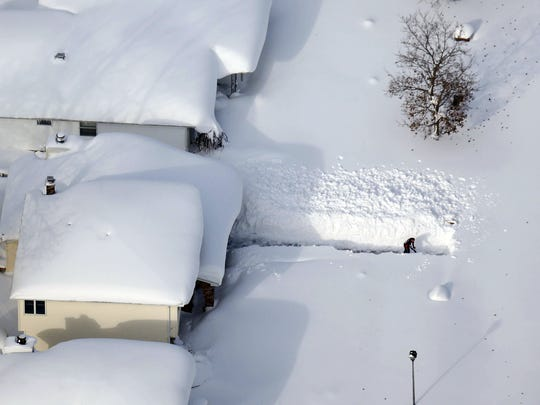 A man digs out his driveway in Depew, Erie County on
