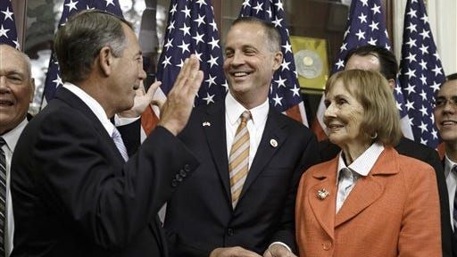 Rep. Curt Clawson, R-Fla., center, participates in a ceremonial swearing-in with House Speaker John Boehner of Ohio, left, and his mother, Cherie Clawson, on Capitol Hill in Washington, Wednesday, June 25, 2014. Clawson won a special election in southwest Florida on Tuesday to replace former Rep. Trey Radel, who resigned in January after pleading guilty to cocaine possession. Clawson will now serve the remainder of Radel's term but must face voters again in November to win re-election.  (AP Photo/J. Scott Applewhite)