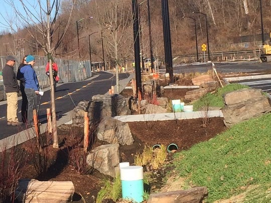 A vegetated stormwater treatment swale nears completion between the Burlington bike path and Lake Street on Nov. 20, 2015.