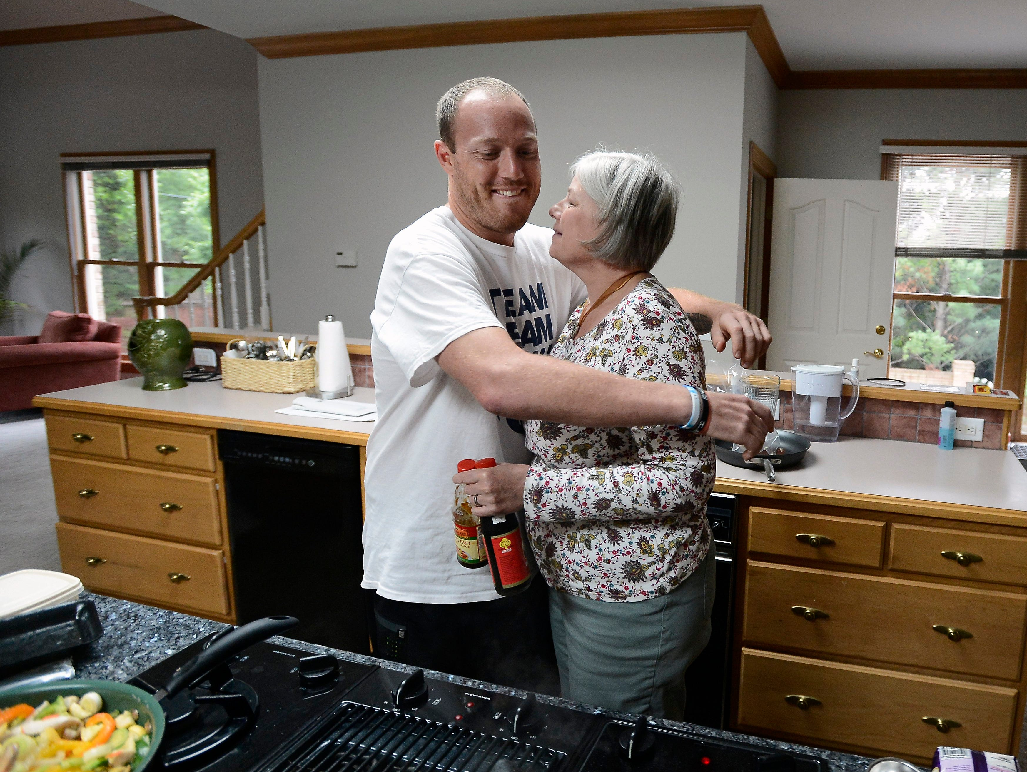 Tim Shaw gives his mom, Sharon, a hug while she cooks dinner on Tuesday, June 2, 2015, in Nashville Tenn.