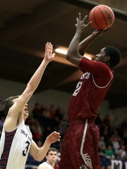 New Mexico State's Braxton Huggins, right, shoots over Saint Mary's Emmett Naar during the first half of an NCAA college basketball game in the first round of the men's NIT on Tuesday, March 15, 2016, in Moraga, Calif.