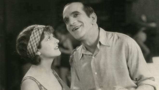 """Al Jolson (right, shown with May McAvoy), stars in """"The Jazz Singer."""""""